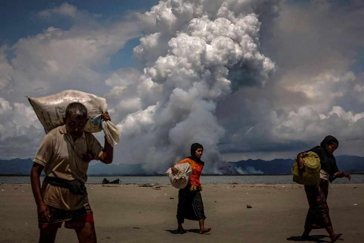 Smoke is seen on the Myanmar border as Rohingya refugees walk on the shore after crossing the Bangladesh-Myanmar border by boat through the Bay of Bengal, in Shah Porir Dwip, Bangladesh, on Sept 11, 2017.