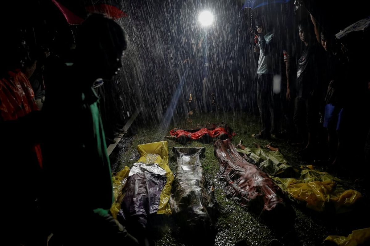 People gather under heavy rain around bodies of Rohingya refugees after the boat they were using to flee violence in Myanmar capsized off Inani Beach near Cox's Bazar, Bangladesh, on Sept 28, 2017.