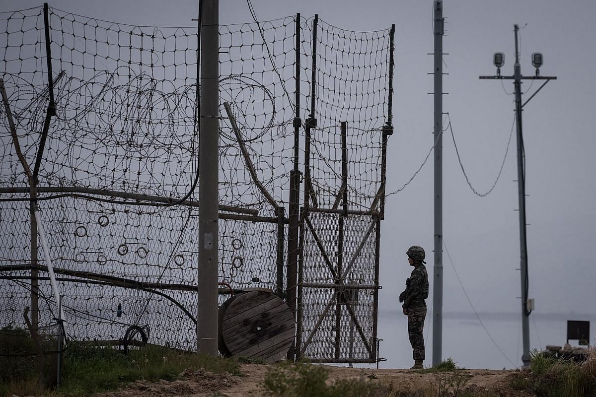 A South Korean soldier standing guard at an opening to the fence of the Demilitarised Zone (DMZ) on Gyodong, a tiny outlying island near to the west of Seoul. At its closest point, Gyodong island lies barely 2km from North Korea, with residents subje