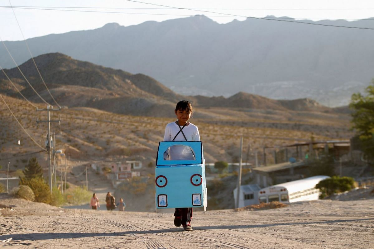 Jazmin, 9, carries a cardboard car to be used in a play in her school at Anapra neighborhood in Ciudad Juarez, Mexico April 16, 2018. PHOTO: REUTERS