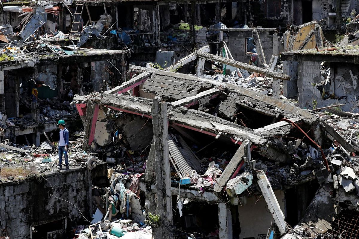 Residents walk through the ruins of their houses, after they were allowed to return to their homes for the first time since the battle between government troops and Islamic State militants began on May 2017, at the Islamic city of Marawi, Philippines