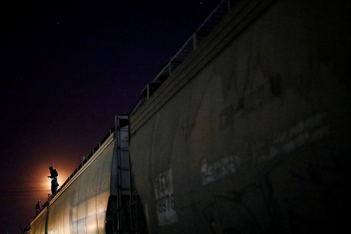 A Central American migrant, moving in a caravan through Mexico, stands on a wagon of a freight train as he embarks on a new leg of their travels, in Tlaquepaque, in Jalisco state, Mexico April 19, 2018. PHOTO: REUTERS