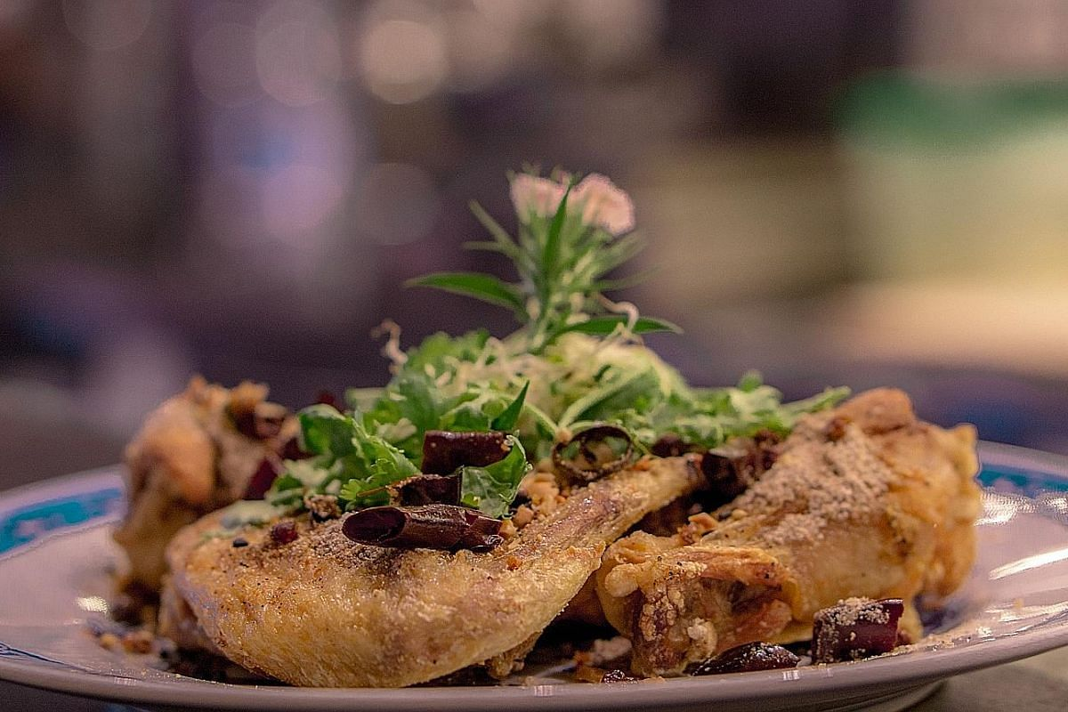 The Whole Fish Asian Style (left) consists of a sea bass that is deep fried and covered with fried garlic and shallot and just a touch of ginger juice. (Below) The Chong Qing Wings are topped with sauteed onions and dried chilli.