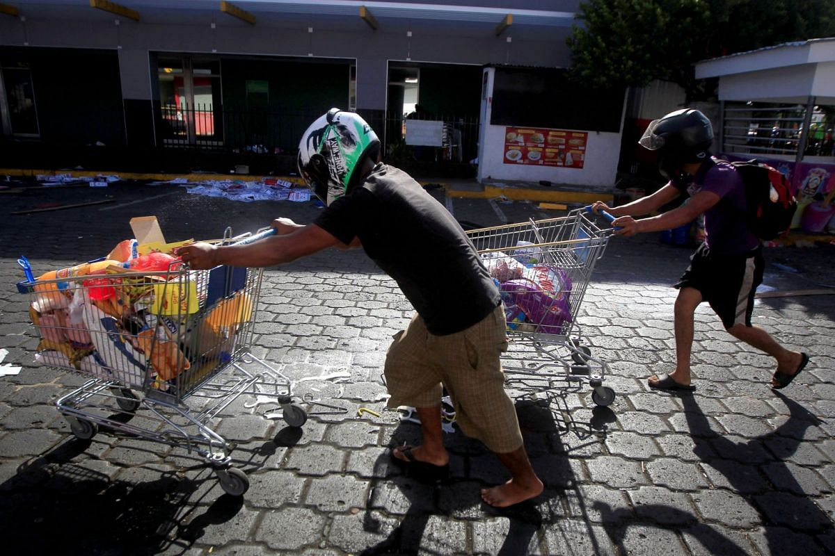 People push shopping trolleys with goods looted from a store after protests over a reform to the pension plans of the Nicaraguan Social Security Institute (INSS) in Managua, Nicaragua, on April 22, 2018.