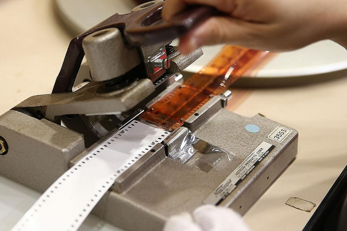 A damaged leader - the length of film attached to the head or tail of a film to assist in threading a projector - is replaced with a new leader using a film splicer. A reel of brittle 16mm film that has shrunk and warped. A film in this state can no