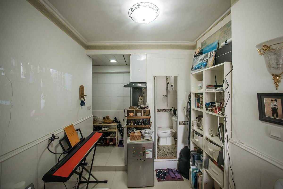 An electric piano, fridge and toilet seen inside a subdivided apartment in Hong Kong.