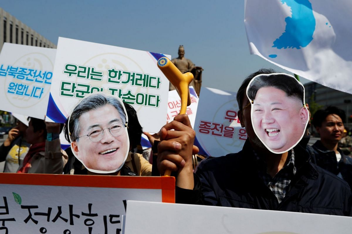 People wear masks of South Korea's President Moon Jae-in and North Korea's leader Kim Jong Un during a pro-unification rally ahead of the upcoming summit between North and South Korea in Seoul, South Korea April 25, 2018.