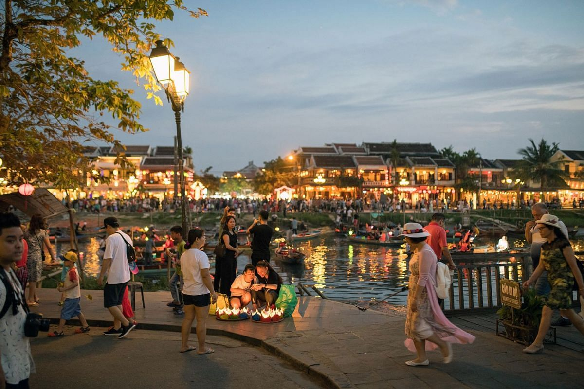 Tourists walk along the Thu Bon River in the old town of Hoi An, Quảng Nam Province, Vietnam, on Friday, April 18, 2018. With a fast-growing economy and a young population, Vietnam offers an attractive market for retailers. Its economy expanded 7.4