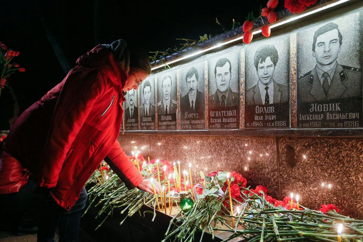 A Ukrainian lights a candle at the memorial for 'liquidators' who died during cleaning up works after the Chernobyl nuclear power plant disaster during a ceremony in Slavutich city, Ukraine, early 26 April 2018. In the early hours of 26 April 1986 th