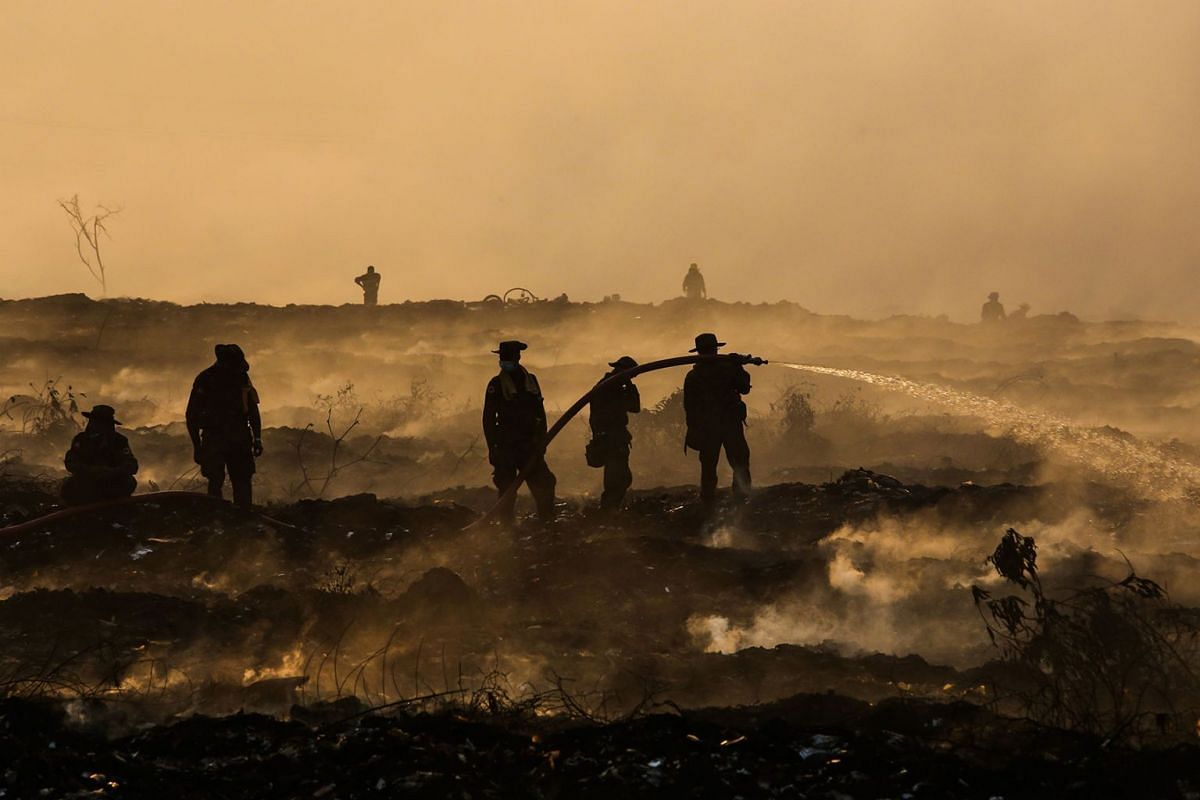 Soldiers are deployed to reinforce 450 firemen battling fire in a massive garbage dump in Yangon on April 25, 2018 that started April 21 blanketing parts of commercial hub with foul smelling smoke. PHOTO: AFP