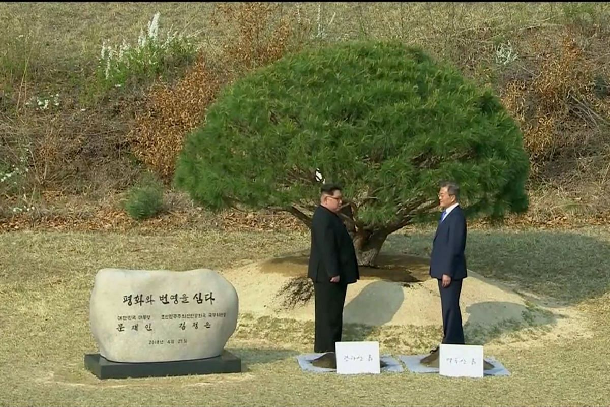 South Korean President Moon Jae In and North Korean leader Kim Jong Un attend a tree planting ceremony during the inter-Korean summit at the truce village of Panmunjom, on April 27, 2018.
