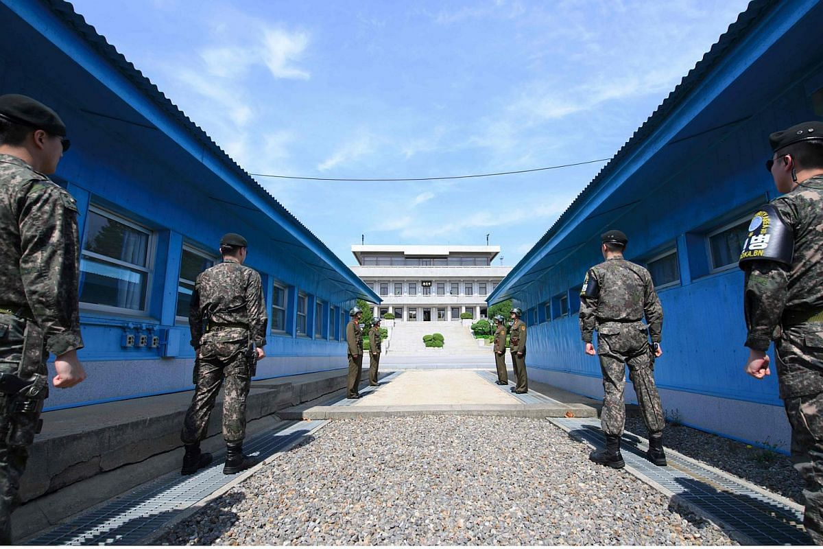 South Korean soldiers (front) and North Korean soldiers (rear) stand guard before the military demarcation line on the each side of the truce village of Panmunjom in the demilitarised zone (DMZ) dividing the two Koreas on April 26, 2018.