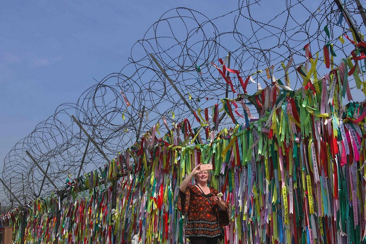 A military fence covered with ribbons with inscriptions calling for peace and reunification at Imjingak peace park in Paju near the demilitarised zone dividing the two Koreas on April 26, 2018.