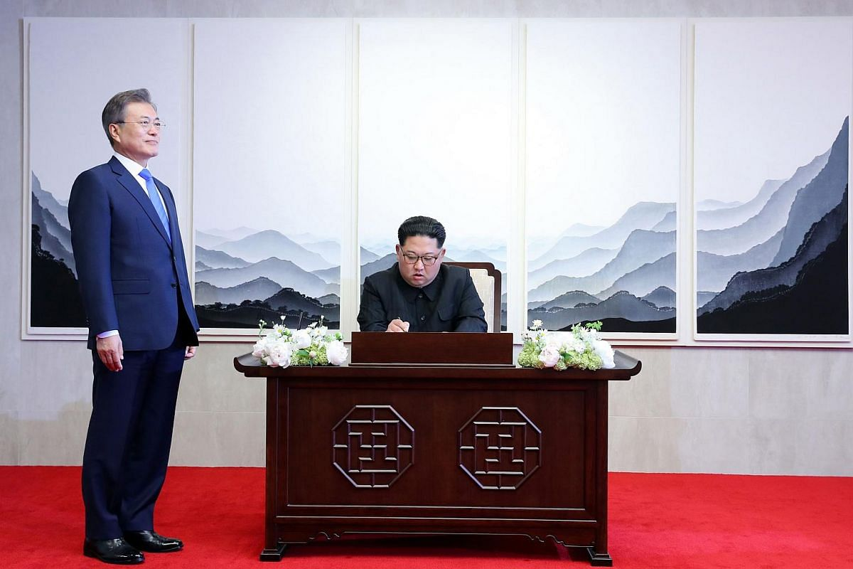 North Korea's leader Kim Jong Un (centre) signs the guest book next to South Korea's President Moon Jae In during the Inter-Korean summit, on April 27, 2018.