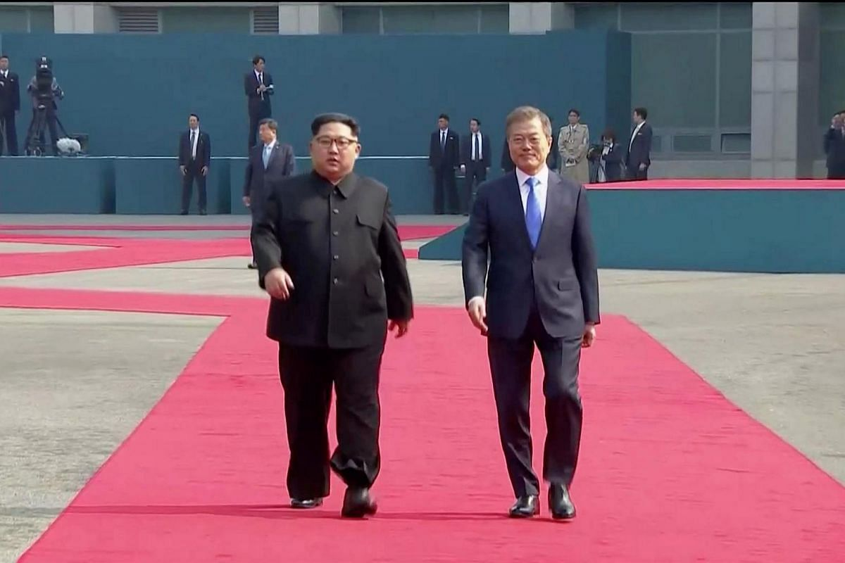 South Korean President Moon Jae In (right) and North Korean leader Kim Jong Un walk on the red carpet during a welcome ceremony at the inter-Korean summit at the truce village of Panmunjom, South Korea on April 27, 2018.