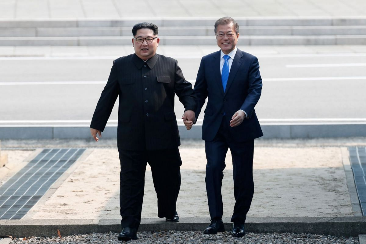North Korean leader Kim Jong Un (left) and South Korean President Moon Jae in walk across the military demarcation line ahead of the inter-Korean summit at the truce village of Panmunjom, South Korea, on April 27, 2018.