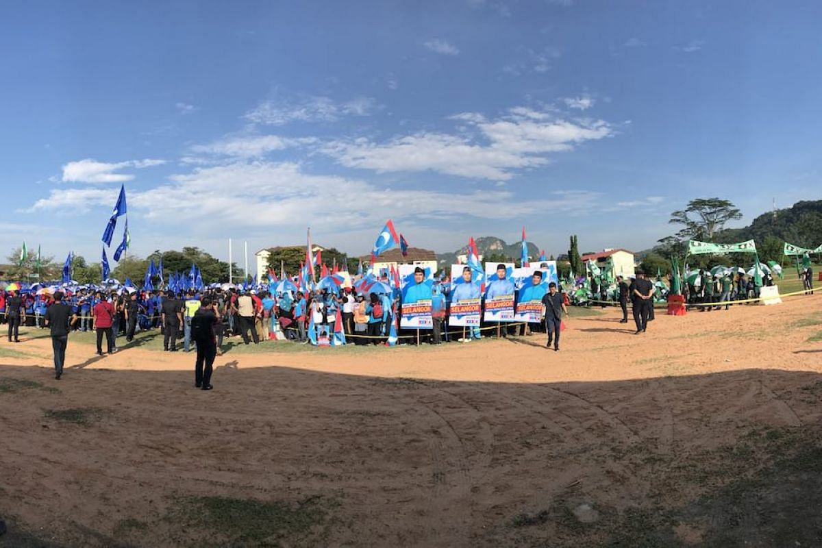 Supporters of different parties wait at a field outside the nomination centre for Hulu Kelang, Gombak Setia, Sungai Tua state seats and Gombak parliament seat.