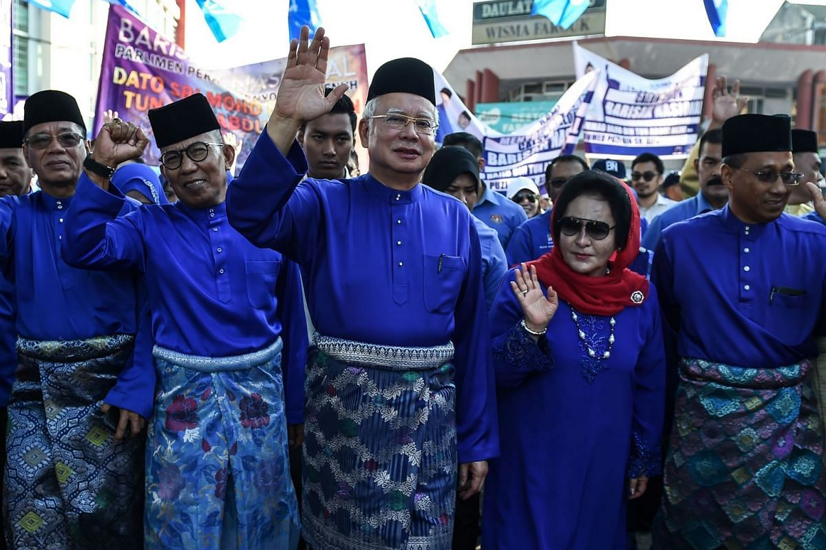 Malaysia's Prime Minister Najib Razak (centre) and his wife Rosmah Mansor arrive at the nomination centre to hand over election documents in Pekan, on April 28, 2018.
