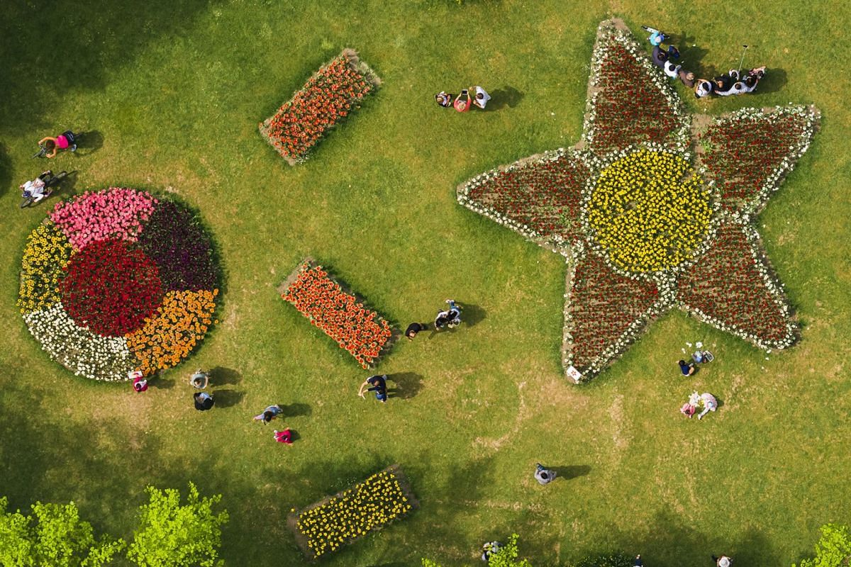 The image taken with a drone shows people enjoying the warm weather as they visit the tulip festival in the Parc de l'Independance in Morges, Switzerland, April 29, 2018. About 120,000 tulips of 300 varieties are in full bloom.
