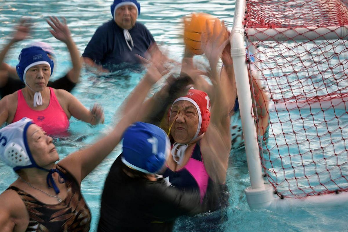 Madam Lee Huang (centre in red cap) blocks the ball at the mouth of the goal.