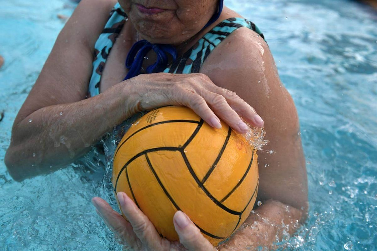 Madam Tan Kak Huay tightly holding onto the ball while trying to fend off an opponent during a game of Flippa Ball at the Toa Payoh Swimming Complex.