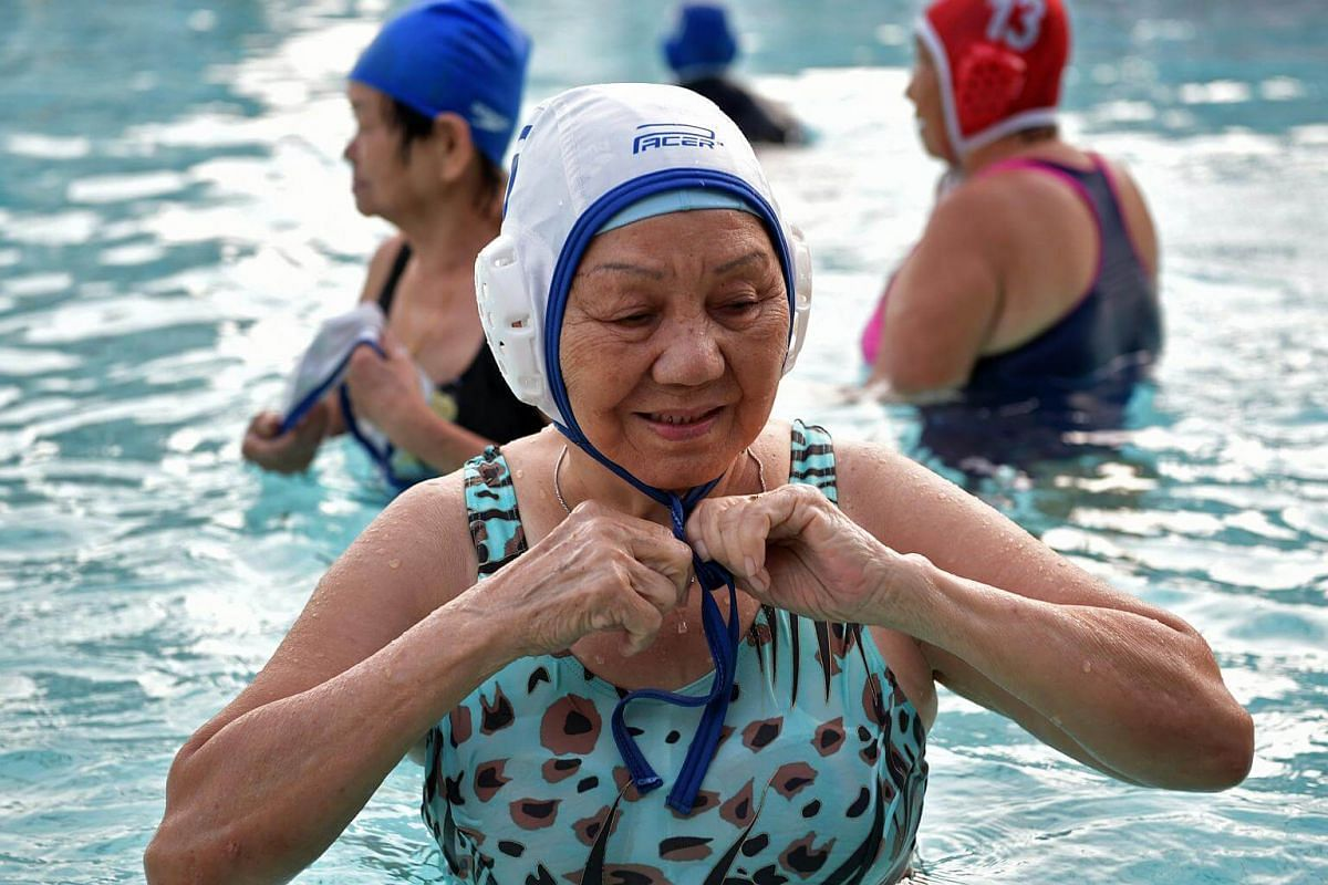 Madam Tan Kak Huay puts on her water polo cap before the game of Flippa Ball at the Toa Payoh Swimming Complex.