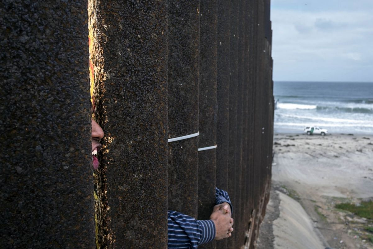 "Central American migrants travelling in the ""Migrant Via Crucis"" caravan demonstrate at the US/Mexico Border at Tijuana's beaches, Baja California state, Mexico, on April 29, 2018. The US has threatened to arrest around 100 Central American migrants"