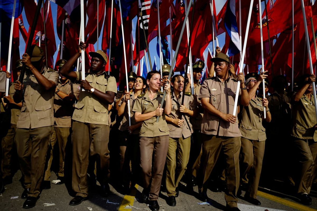 Army soldiers carry flags during the May Day rally in Havana, Cuba, May 1, 2018.