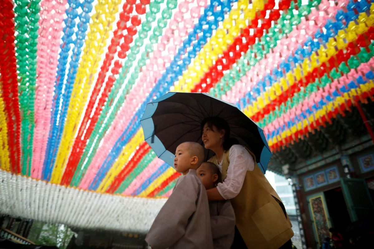 Novice monks walk underneath lotus lanterns bearing prayer petitions as they leave after an event to celebrate the upcoming Vesak Day, the birthday of Buddha, at Jogye temple in Seoul, South Korea, May 2, 2018.