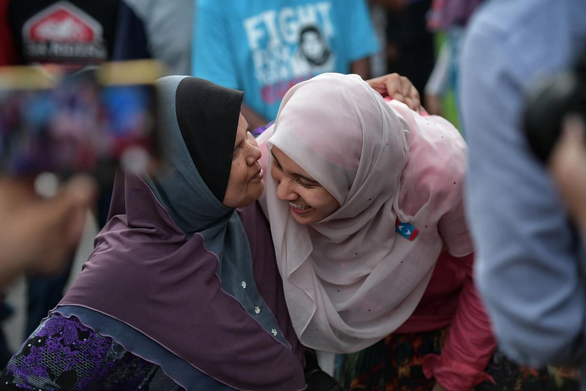 PKR candidate Nurul Izzah Anwar receives a kiss from blind busker Ainun during a walkabout at a pasar malam in Permatang Pauh, on May 1, 2018.
