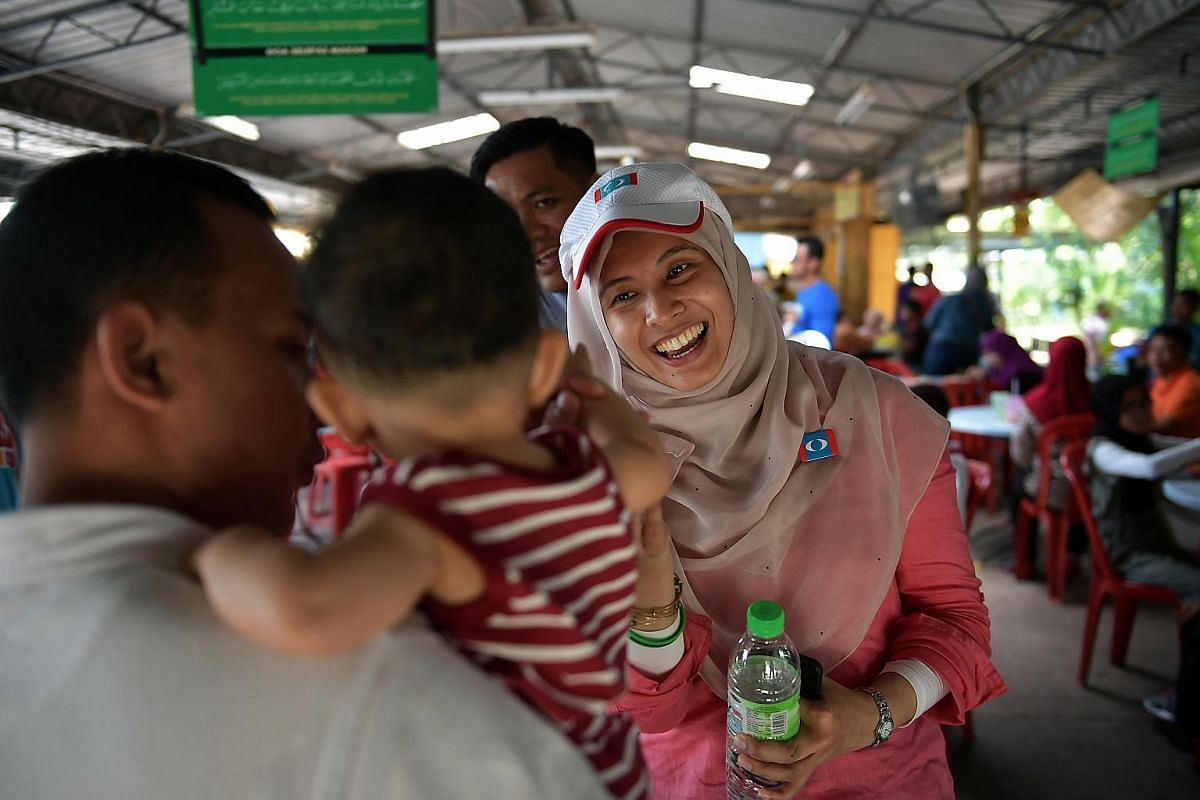 PKR candidate Nurul Izzah Anwar meeting residents during her walkabout at the Kedia Nasi Campur stall in Permatang Pauh on mainland Penang as fellow Permatang Pauh candidate Afif Bahardin looks on May 1,2018.