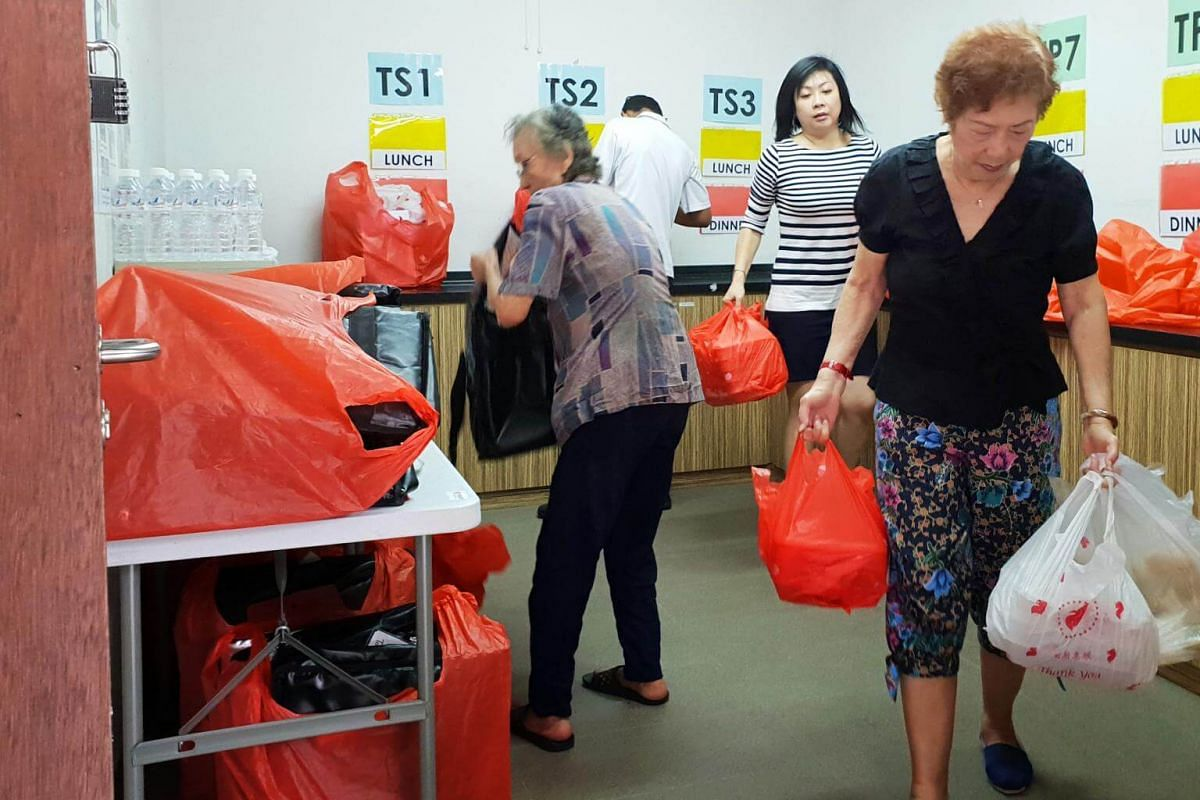 Nancy Leow (right) and her daughter Nora Lim (second from right) leaving Touch Home Care's centre in Lorong 1 Toa Payoh after packing the meals into individual plastic bags. They will then drive to the resident's home to deliver the dinner.