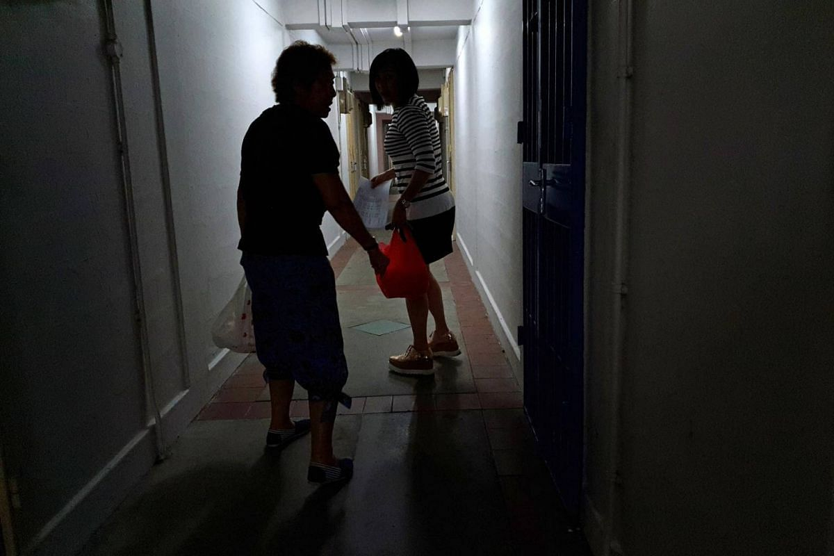 Nora Lim (back) and her mother Nancy Leow delivers dinner to some of the residents in block 5 in Lorong 7 Toa Payoh. The corridor is often dark, hot and humid.