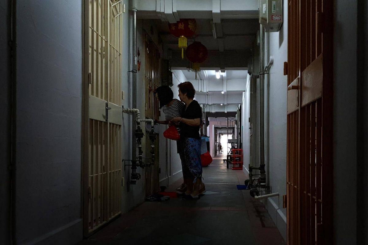 Nora Lim (back) and her mother Nancy Leow speaking with one of the residents whom they deliver the dinner to, in block 5 in Lorong 7 Toa Payoh.