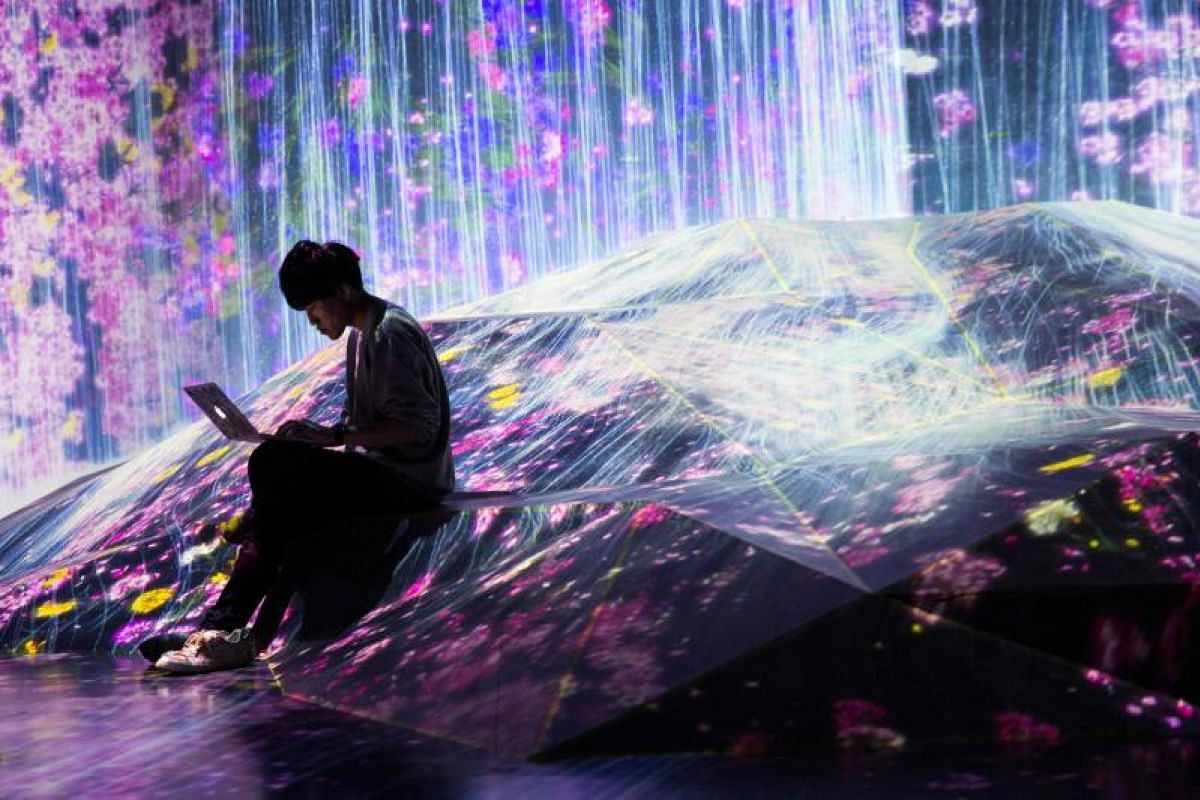 A member of teamLab collective works on his laptop in a digital installation waterfall room, filled with flowers which appears to flow over a hill, at Mori Building Digital Art Museum in Tokyo on May 1, 2018.