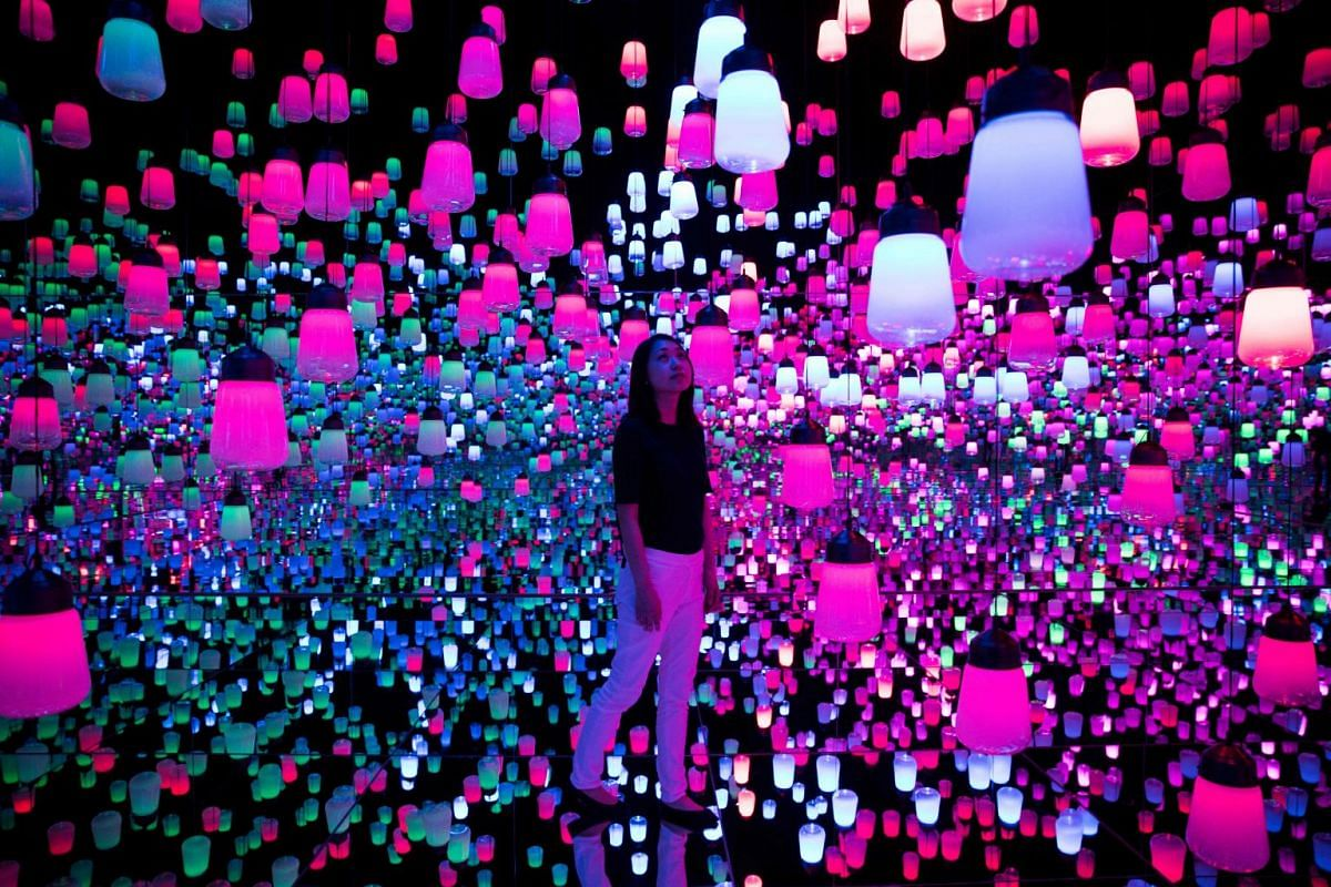 In this picture taken on May 1, 2018 a Japanese member of teamLab collective walks and poses in a digital installation room with hanging lamps that illuminate as the visitor nears at Mori Building Digital Art Museum in Tokyo.