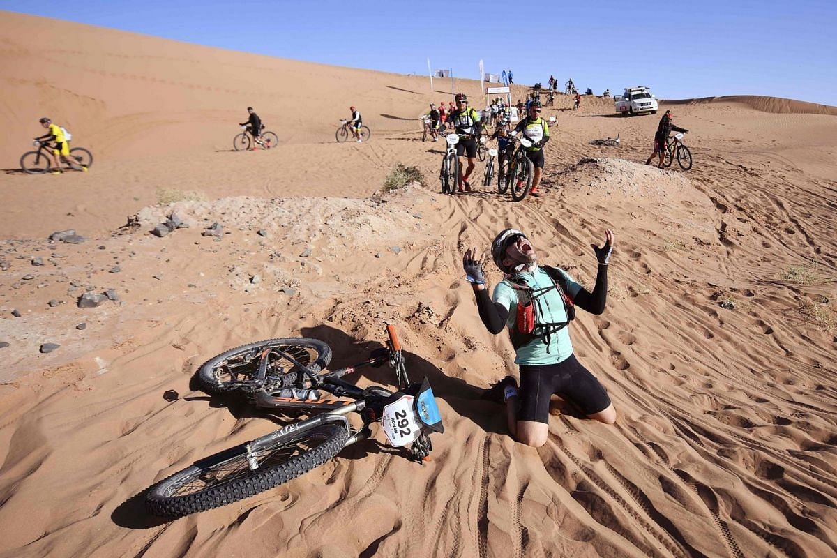 A competitor reacts after crossing a sand dune during Stage 4 of the 13th edition of the Titan Desert 2018 mountain biking race between Boumalne Dades and Merzouga in Morocco on May 2, 2018. The Titan Desert 2018 is 600 kilometre mountain bike race