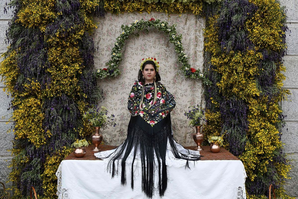 """Natalia Ciriza Berrocal takes part in the """"Las Mayas"""" festival in Colmenar Viejo near Madrid, Spain, on May 2, 2018. The Mayas, young girls aged between 7 and 11, are required to sit still in a decorated altar derived from pagan rites celebrating the"""