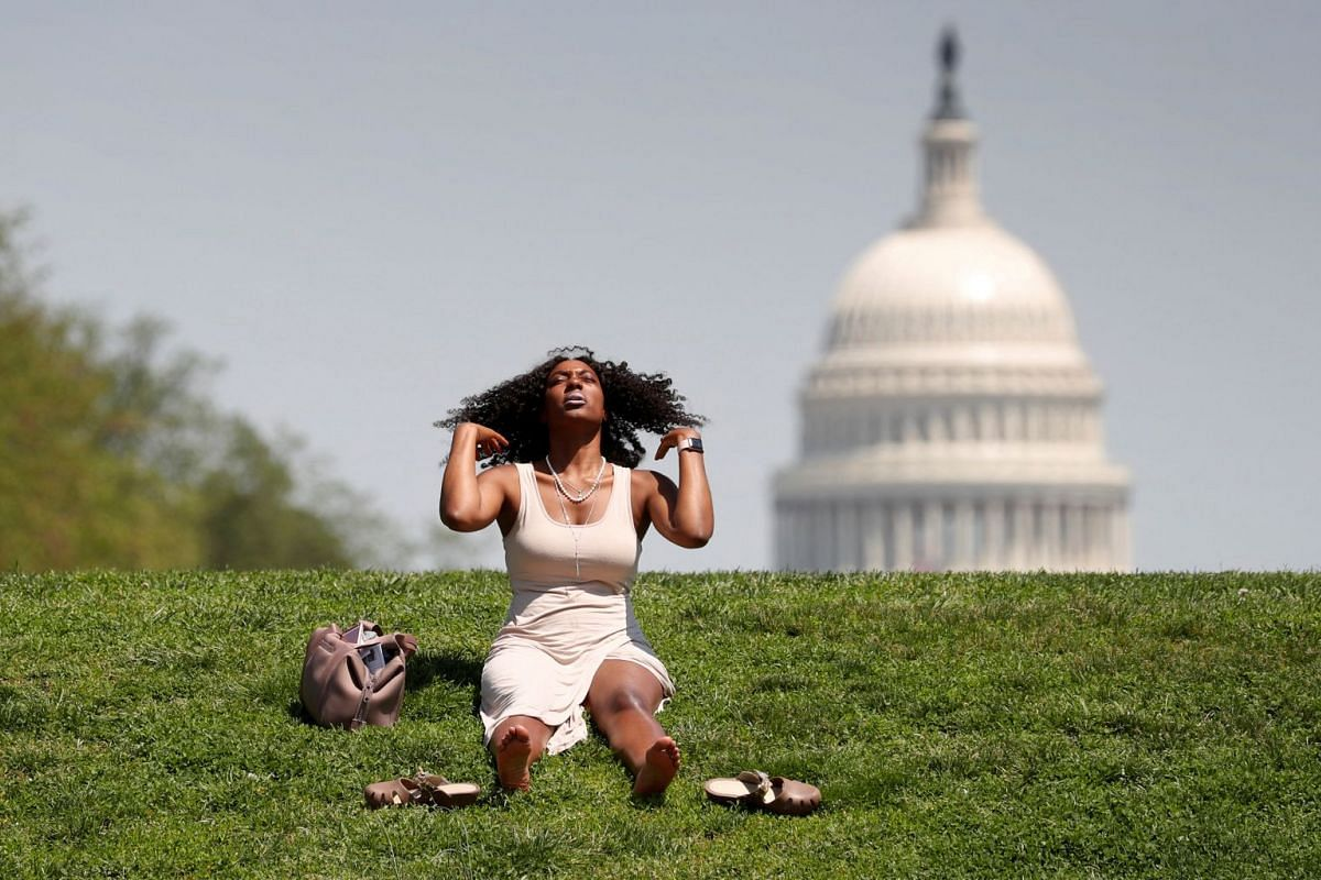 With the U.S. Capitol in the background, Kellye Sims flips her hair up as she basks in the sun, at the National Mall, during a record-setting heat wave in Washington, D.C., U.S., May 3, 2018.