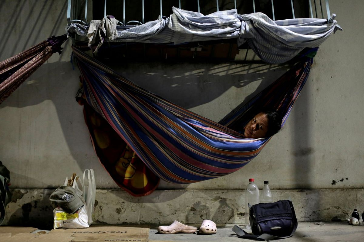 Venezuelan refugee Gabriela Martinez, who worked as a telecommunications engineer, relaxes in a hammock near a bus station in Manaus, Brazil, May 1, 2018.