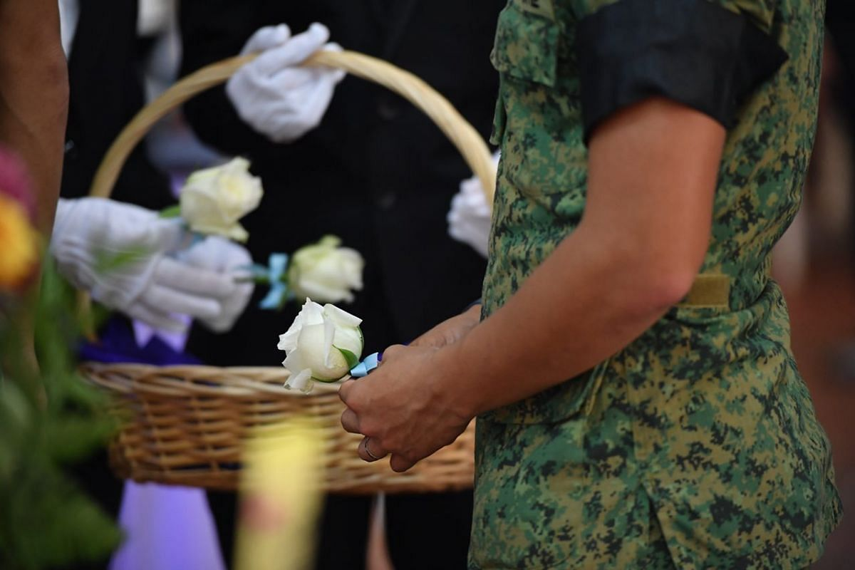 An army personnel holding a flower while paying his last respects to Corporal First Class Dave Lee Han Xuan.
