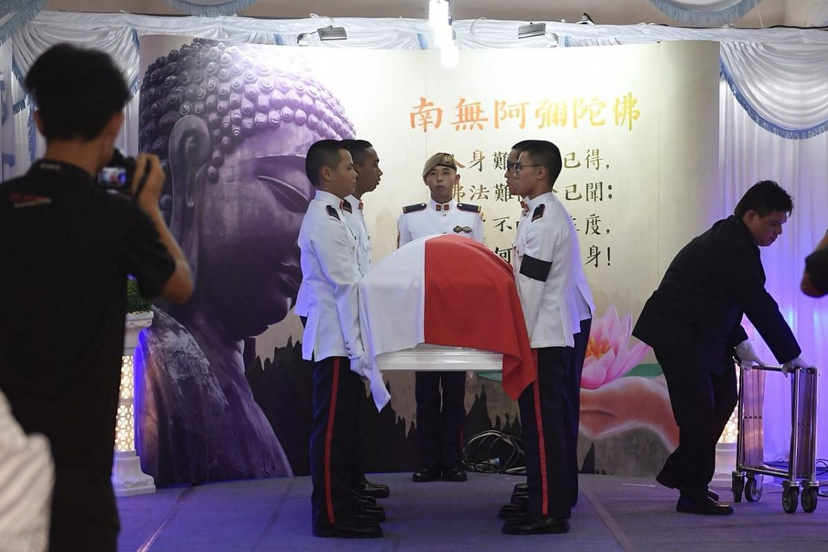 Army personnel bearing the coffin of Corporal First Class Dave Lee Han Xuan, draped with the state flag.