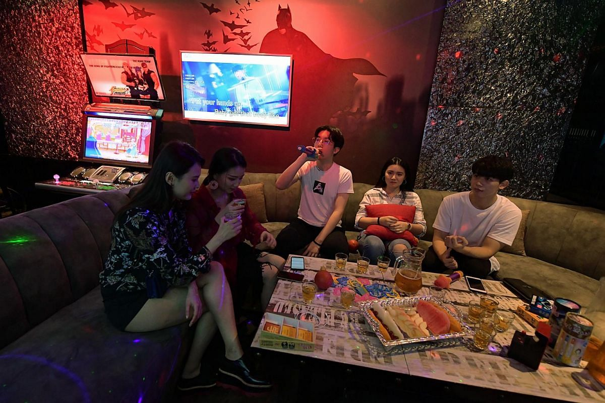 A Batman-themed deluxe room at HaveFun Karaoke in Bugis Cube with amenities like board games and an arcade machine.