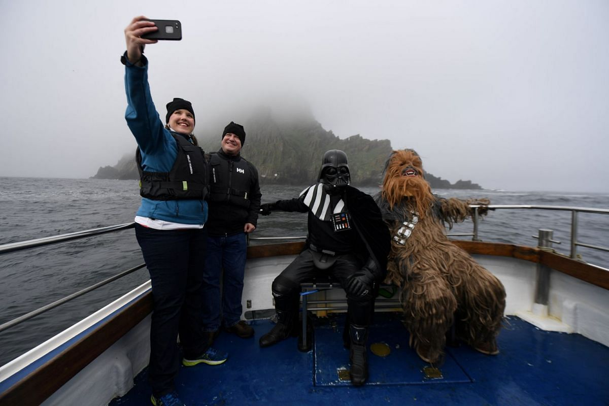 Holidaymakers take a selfie, along with Star Wars fans dressed in costume as Darth Vader and Chewbacca, on a boat trip to Skellig Island during the inaugural 'May The 4th Be With You' festival in the County Kerry village of Portmagee, Ireland, May 4,