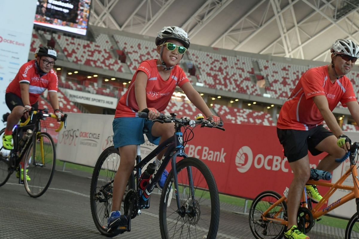 A young participant wearing shades as he cycles inside the Singapore Sports Hub.