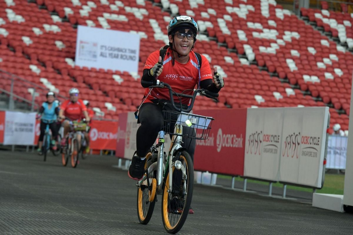 A rider giving the thumbs up as he cycles inside the Singapore Sports Hub.
