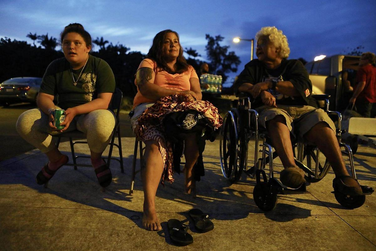 (From left) Evacuees Anastasia de Sousa, Nina Bermasina and Aunty Willy Kamalamalama de Sousa sit outside the emergency shelter where they are staying at the Pahoa Community Center on Hawaii's Big Island on May 5, 2018.