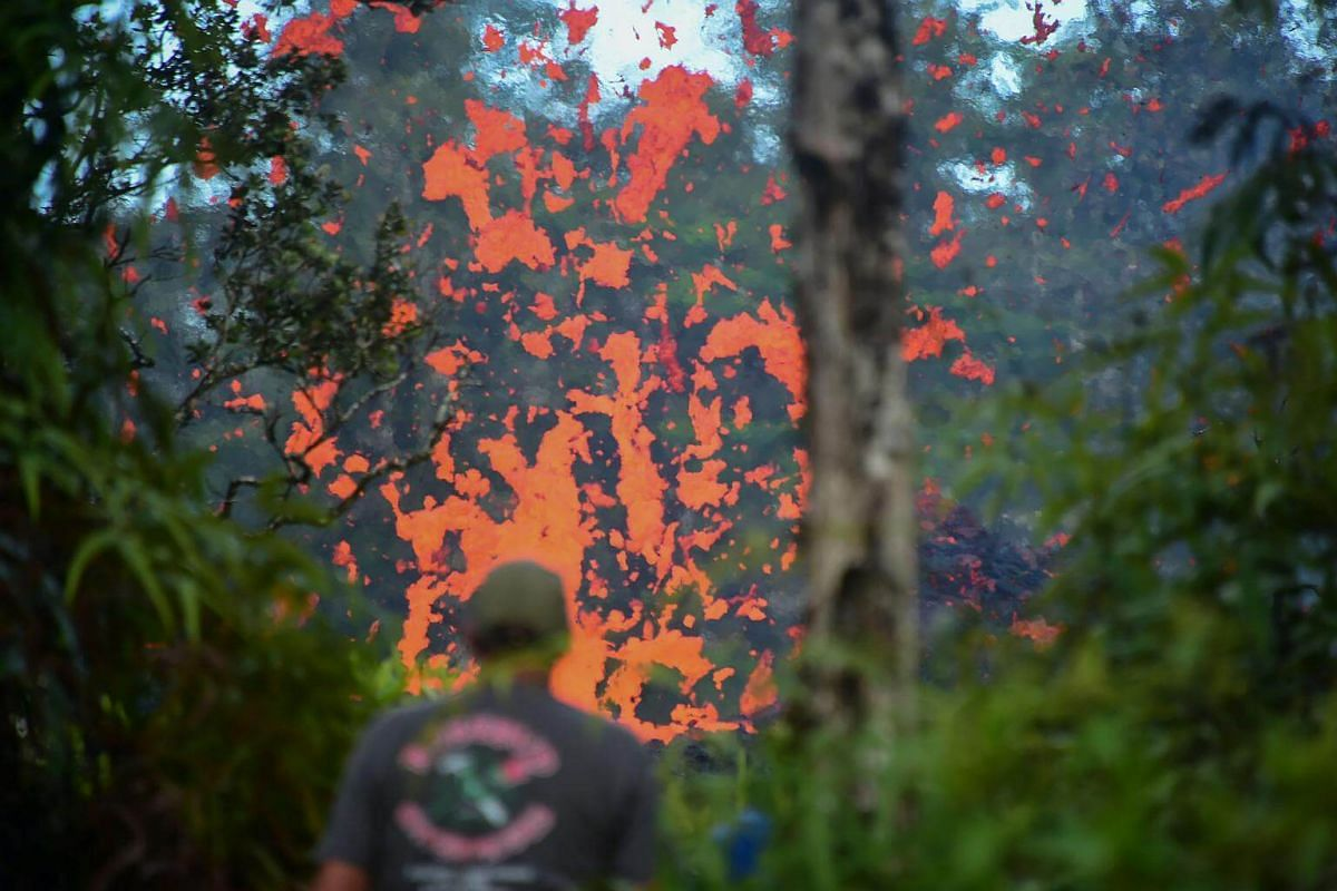 A man watches as lava is seen coming from a fissure in Leilani Estates subdivision on Hawaii's Big Island, on May 4, 2018.