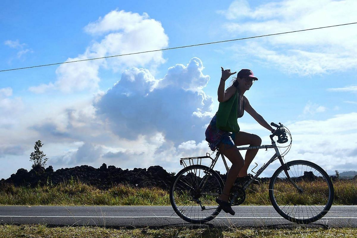 A cyclist offers the Shaka sign while riding past a plume of volcanic smoke in the distance over the area of Leilani Estates near the town of Pahoa, on May 6, 2018.