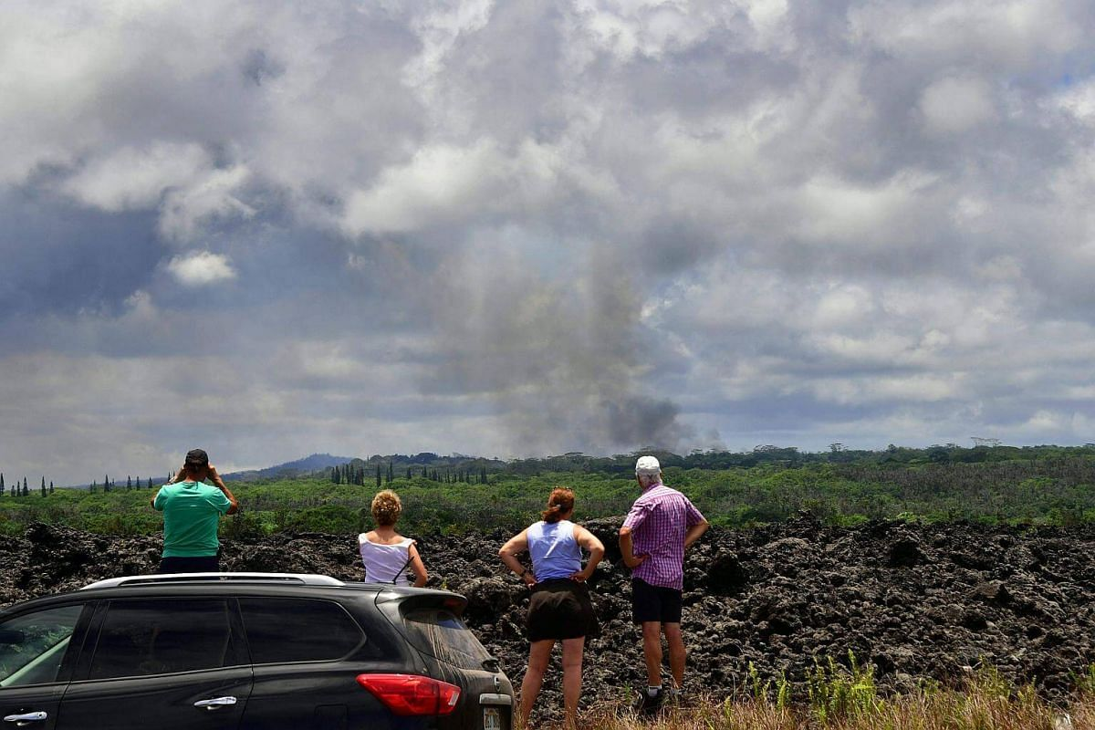 People stop their vehicle on the side of the road for a view of a plume of smoke rising over the area of Leilani Estates, on May 6, 2018.
